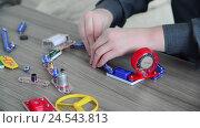 Купить «Boy assembles the electrical circuit from constructor», видеоролик № 24543813, снято 10 декабря 2016 г. (c) Володина Ольга / Фотобанк Лори
