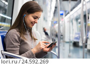 Купить «brunette girl using cell phone and smiling at subway», фото № 24592269, снято 24 мая 2018 г. (c) Яков Филимонов / Фотобанк Лори