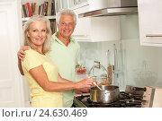 Senior Couple Preparing Meal At Cooker. Стоковое фото, фотограф Monkey Business Images Ltd / easy Fotostock / Фотобанк Лори