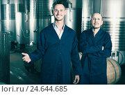 Купить «Two smiling men in uniforms standing in winery fermentation compartment», фото № 24644685, снято 15 сентября 2019 г. (c) Яков Филимонов / Фотобанк Лори