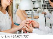 Купить «Female client doing nails in nail salon in close-up», фото № 24674737, снято 2 ноября 2016 г. (c) Яков Филимонов / Фотобанк Лори