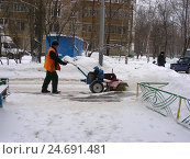 Купить «Рабочий коммунальной службы чистит дорогу от снега снегоуборочной техникой во дворе жилых домов на Хабаровской улице в Гольянове в Москве», эксклюзивное фото № 24691481, снято 15 февраля 2012 г. (c) lana1501 / Фотобанк Лори