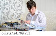 Купить «Teen boy collects constructor in room», видеоролик № 24709733, снято 18 декабря 2016 г. (c) Володина Ольга / Фотобанк Лори