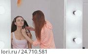 Makeup artist applying liquid tonal foundation on the face of the woman. Стоковое видео, видеограф Aleksey Popov / Фотобанк Лори