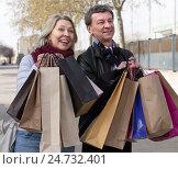 Купить «Счастливая пожилая пара с бумажными пакетами в руках стоит на городской улице», фото № 24732401, снято 23 марта 2016 г. (c) Татьяна Яцевич / Фотобанк Лори