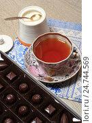 Купить «Шоколадные конфеты в коробке и чашка чая на столе», эксклюзивное фото № 24744569, снято 21 декабря 2016 г. (c) Яна Королёва / Фотобанк Лори