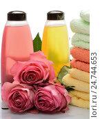 Разноцветные предметы для бани, сауны, спа: шампунь, полотенца, розы на белом фоне. Стоковое фото, фотограф VIACHESLAV KRYLOV / Фотобанк Лори