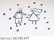 Два золотых обручальных кольца лежат на детском рисунке с молодожёными. Стоковое фото, фотограф Игорь Низов / Фотобанк Лори