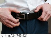 Купить «Мужчина застегивает ремень на брюках», эксклюзивное фото № 24745421, снято 12 ноября 2016 г. (c) Игорь Низов / Фотобанк Лори