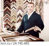 Купить «portrait of man seller working with picture frames in atelier», фото № 24745485, снято 16 ноября 2019 г. (c) Яков Филимонов / Фотобанк Лори