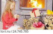 Купить «Happy nice girl opening christmas present near fireplace», видеоролик № 24745785, снято 14 ноября 2016 г. (c) Дмитрий Травников / Фотобанк Лори
