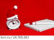 Купить «Часы в новогоднем колпаке, блокнот и ручка на ярком красном фоне. Новогодний бизнес-натюрморт», фото № 24765061, снято 23 декабря 2016 г. (c) Наталья Осипова / Фотобанк Лори
