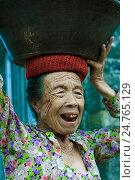 Портрет улыбающейся азиатской пожилой женщины с испорченными зубами которая несет керамический кувшин на голове, фото № 24765129, снято 8 ноября 2008 г. (c) Эдуард Паравян / Фотобанк Лори