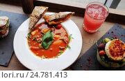 Купить «gazpacho soup, salad and drink at restaurant», видеоролик № 24781413, снято 29 сентября 2016 г. (c) Syda Productions / Фотобанк Лори