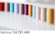 Купить «row of colorful thread spools on table», видеоролик № 24781469, снято 3 октября 2016 г. (c) Syda Productions / Фотобанк Лори