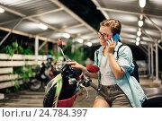Купить «Молодая счастливая девушка с мобильным телефоном на мотороллере», фото № 24784397, снято 3 декабря 2016 г. (c) Галаганов Дмитрий Александрович / Фотобанк Лори