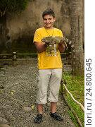 Подросток  показывает варана в парке птиц на острове Бали в Индонезии, фото № 24800645, снято 10 ноября 2008 г. (c) Эдуард Паравян / Фотобанк Лори