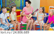 Купить «Children sitting with teacher and listening to music in class», фото № 24806689, снято 23 мая 2018 г. (c) Яков Филимонов / Фотобанк Лори