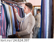 Smiling guy deciding on new shirt in men's cloths store. Стоковое фото, фотограф Яков Филимонов / Фотобанк Лори