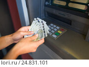 Купить «close up of hand withdrawing money at atm machine», фото № 24831101, снято 8 сентября 2016 г. (c) Syda Productions / Фотобанк Лори