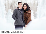 Winter wedding, the bride with veil, groom in wintry clothes on the street in the middle of ice figures and snow, looking at camera smiling. Стоковое фото, фотограф Евгений Майнагашев / Фотобанк Лори