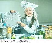 Купить «Girl in cook cap holding clock at domestic kitchen», фото № 24846905, снято 20 ноября 2019 г. (c) Яков Филимонов / Фотобанк Лори