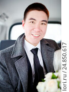 Купить «The groom in a winter coat sitting in the car with wedding bouquet in hands. Positive portrait, looking into the camera.», фото № 24850617, снято 20 февраля 2016 г. (c) Евгений Майнагашев / Фотобанк Лори