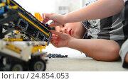 Купить «Kid plays with toy excavator from constructor», видеоролик № 24854053, снято 8 января 2017 г. (c) Володина Ольга / Фотобанк Лори