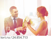 smiling man giving flower bouquet at restaurant. Стоковое фото, фотограф Syda Productions / Фотобанк Лори