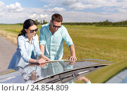 Купить «happy man and woman with road map on car hood», фото № 24854809, снято 12 июня 2016 г. (c) Syda Productions / Фотобанк Лори