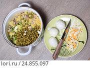Вареные яйца целые и нарезанные на тарелке, нож и кастрюля с салатом оливье. Стоковое фото, фотограф Яна Королёва / Фотобанк Лори