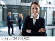 Купить «Portrait of businesswoman standing with arms crossed», фото № 24859625, снято 6 июля 2016 г. (c) Wavebreak Media / Фотобанк Лори