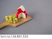 Купить «Gouda cheese with grapes on chopping board», фото № 24861533, снято 16 сентября 2016 г. (c) Wavebreak Media / Фотобанк Лори