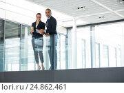 Купить «Business colleagues standing at office corridor», фото № 24862461, снято 6 июля 2016 г. (c) Wavebreak Media / Фотобанк Лори