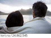 Купить «Rear view of couple wrapped in shawl on beach», фото № 24862545, снято 29 сентября 2016 г. (c) Wavebreak Media / Фотобанк Лори
