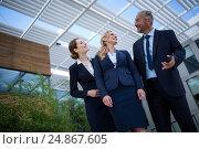 Купить «Confident businesspeople standing in the office premises», фото № 24867605, снято 6 июля 2016 г. (c) Wavebreak Media / Фотобанк Лори
