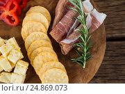 Купить «Cheese, red pepper slices, meat and nacho chips on wooden table», фото № 24869073, снято 16 сентября 2016 г. (c) Wavebreak Media / Фотобанк Лори