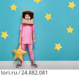 Купить «Child girl in an astronaut costume is playing and dreaming of becoming a spacemen. Portrait of funny kid on a background of bright blue wall with yellow stars.», фото № 24882081, снято 24 декабря 2016 г. (c) Константин Юганов / Фотобанк Лори
