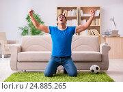 Купить «Man watching football at home sitting in couch», фото № 24885265, снято 22 октября 2016 г. (c) Elnur / Фотобанк Лори