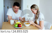 Купить «Happy couple having breakfast», видеоролик № 24893025, снято 18 июля 2019 г. (c) Wavebreak Media / Фотобанк Лори