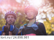 Купить «Biker couple standing together», фото № 24898981, снято 26 марта 2019 г. (c) Wavebreak Media / Фотобанк Лори