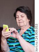 Пожилая женщина с улыбкой набирает СМС на экране смартфона, фото № 24909053, снято 6 января 2017 г. (c) Эдуард Паравян / Фотобанк Лори