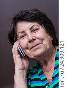 Пожилая женщина говорит по сотовому телефону улыбается и смотрит в кадр, фото № 24909121, снято 6 января 2017 г. (c) Эдуард Паравян / Фотобанк Лори