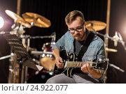 Купить «man playing guitar at studio rehearsal», фото № 24922077, снято 18 августа 2016 г. (c) Syda Productions / Фотобанк Лори