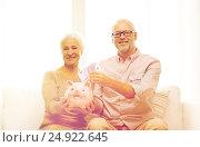 Купить «senior couple with money and piggy bank at home», фото № 24922645, снято 4 сентября 2014 г. (c) Syda Productions / Фотобанк Лори