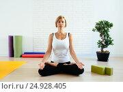 Купить «Woman doing yoga in studio lotus position», фото № 24928405, снято 19 июля 2016 г. (c) Валерий Скурыдин / Фотобанк Лори