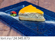 Cheesecake with mango sauce, passion fruit on a blue background. Стоковое фото, фотограф Андрей Черненко / Фотобанк Лори