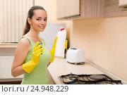 Купить «Young wife cleaning kitchen holding bottle», фото № 24948229, снято 27 сентября 2016 г. (c) Elnur / Фотобанк Лори