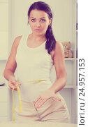 Young sad woman measures waist. Стоковое фото, фотограф Яков Филимонов / Фотобанк Лори