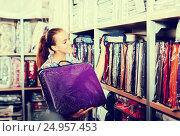Купить «Young female shopper searching for bed linen», фото № 24957453, снято 21 января 2020 г. (c) Яков Филимонов / Фотобанк Лори